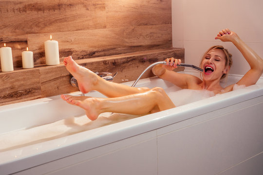 young blonde emotional woman relaxing in bath with foam singing loud