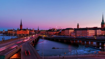 Wall Mural - Stockholm, Sweden. Time-lapse of Gamla Stan in Stockholm, Sweden with landmarks like Riddarholm Church during the sunrise. View of old buildings and car traffic at the bridge, zoom in