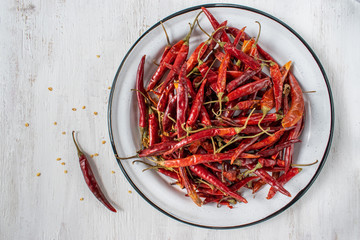 Red Chile de árbol chilis on rustic white background flat lay