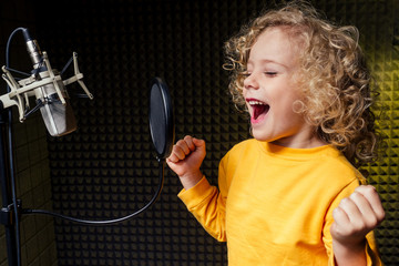 girl blonde curly hair style star singer artist in a yellow blouse with headphone recording new song with microphone.