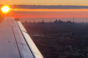 An Air Canada flight approaches Toronto Pearson International Airport as the sun rises over the city of Toronto