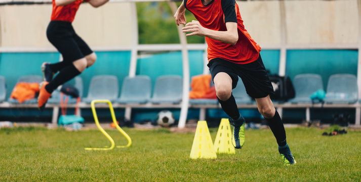 Boy Soccer Player In Training. Boys Running Between Cones amd Jumping During Practice in Field on Sunny Day. Young Soccer Players at Speed and Agility Practice Session