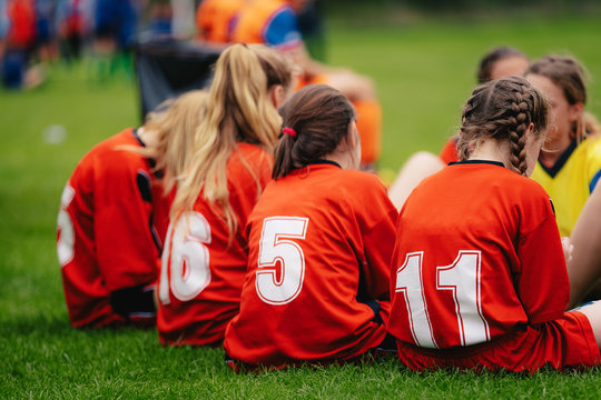 Girls in sports soccer team outdoors. Female physical education class on sports grass field. Young football players of female youth sports team