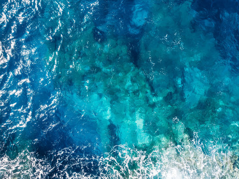 Raging blue water of open Mediterranean Sea with turquoise bottom. top view