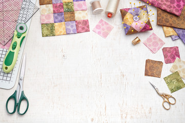 Bright square pieces of fabric, patchwork tools, sewing equipment, traditional quilting