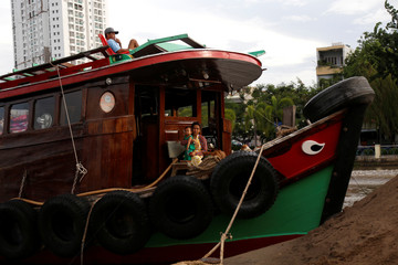 A woman holds a child on a ship carrying sand on the Saigon in Ho Chi Minh city