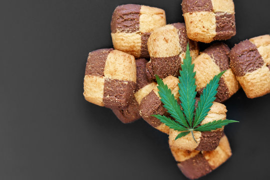 Breakfast with sweet cookies on a dark background with a green leaf of cannabis. Marijuana CBD dessert. Copy space. View from above. Concept of marijuana use for medicinal purposes