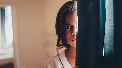 woman peeking behind teal door