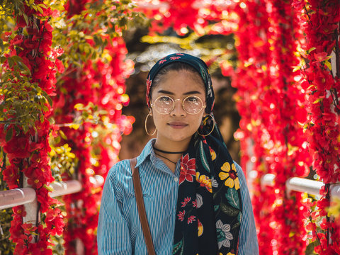 woman standing on front of red flowers