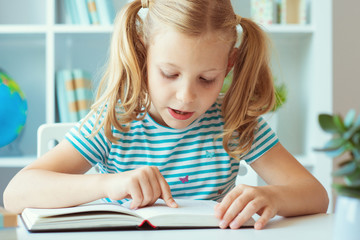 Portrait of a cute little girl read book at the table in classroom