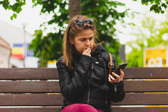 Confused young woman looking at her phone while sitting on a bench in the park – Concern girl wearing a leather jacket with short brown hair holding her smartphone