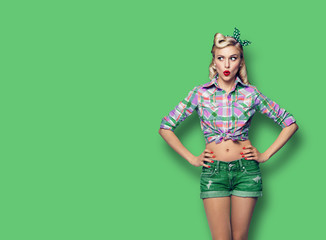 Photo of young surprised woman, looking sideways, dressed in pin-up style, over green color background