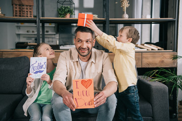 happy children with fathers day gifts having fun with father holding greeting card with i love you dad inscription and heart symbol