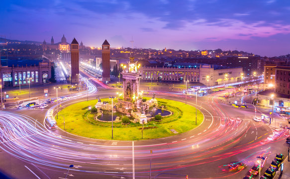 Placa d'Espanya (Plaza de Espana) square in Barcelona, Catalonia, Spain at dusk, after sunset. Beautiful pink glow in the sky and light trails from passing cars on the round about.