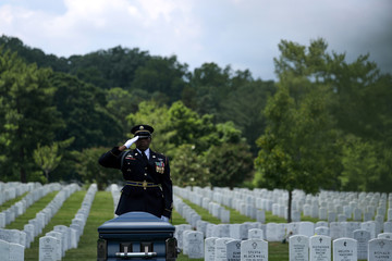 U.S. Army Sergeant Taylor salutes as World War II veteran Mann is laid to rest at Arlington National Cemetery
