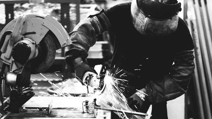Heavy industry worker cutting steel with grinder machine in industrial manufacture, black and white
