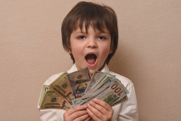 Happy child with money dollar, little businessman. Pile of United States dollar hundred USD banknotes in boy's hand.