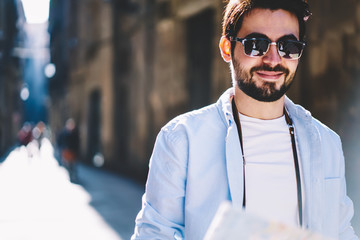Cropped portrait of cheerful handsome bearded tourist smilin at camera while walking outdoors.Positive young man in stylish black sunglasses standing in centre in urban setting near copy space area