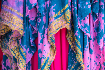 Background of colorful draped overlapping fabrics in pinks and turquoise with gold yellow embroidered design -boho or gypsy look