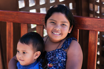 An older sister holding her younger brother tightly while sitting on a wooden bench.