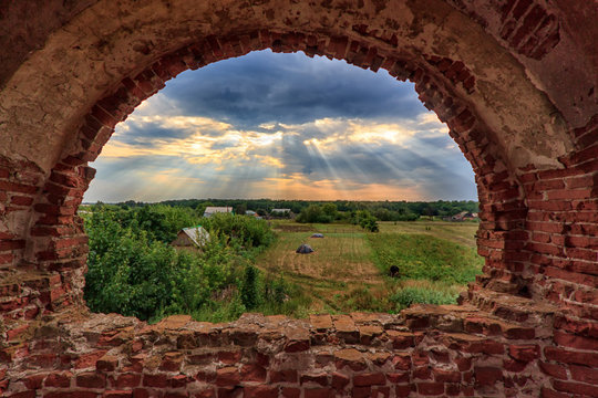 View through the window of an abandoned church in Russia at the village at sunset