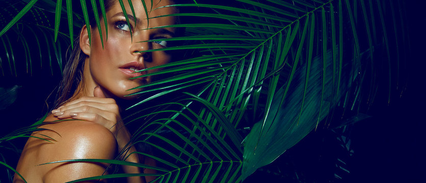 A beautiful tanned girl with natural make-up and wet hair stands in the jungle among exotic plants