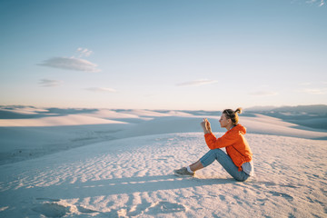 Female traveler making pictures of beautiful desert landscape with white dunes using telephone camera, hipster girl taking photos exploring scenery unique environment in New Mexico during vacations