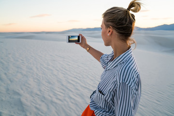 Hipster girl holding mobile phone making picture visiting famous american landmark White sands Park at sunset, back view of young woman using smartphone camera taking photos of scenic nature landscape