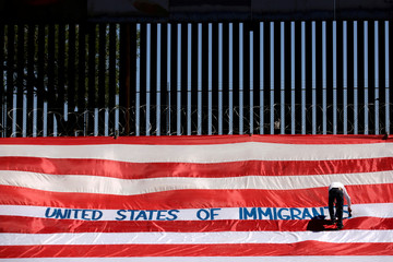 Roberto Marquez, known as Roberz, writes on a large U.S. flag as part of a protest called 'United States of Immigrants', aimed to demand respect for the migrants, near a border wall in El Paso, Texas, as pictured from Ciudad Juarez