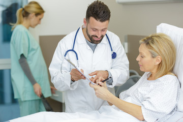 patient in hospital bed signing consent form