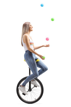 Young woman juggling with balls on a unicycle