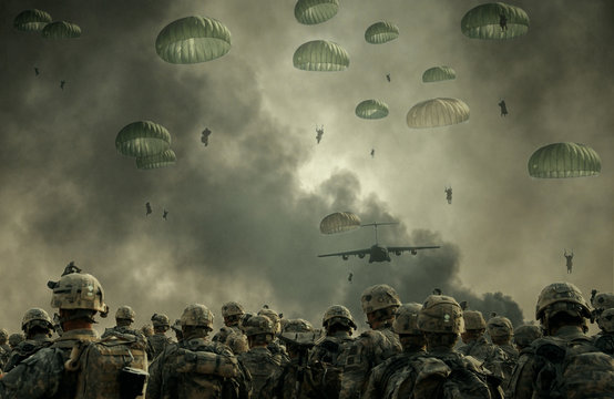 Military helicopter and forces between fire and smoke in destroyed city and soldiers are in flight with a parachute to reach battlefield/Soldiers are looking at them.