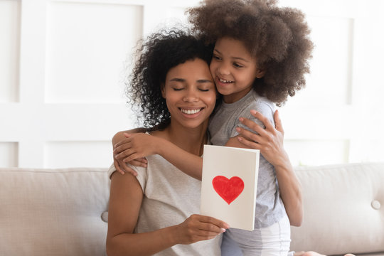 African mum hugging daughter holding greeting card on mothers day