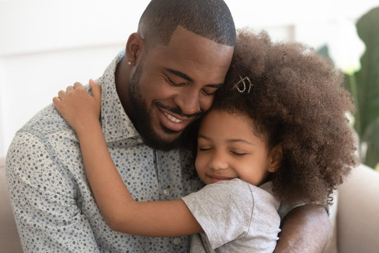 Loving african father hug cute child daughter with eyes closed