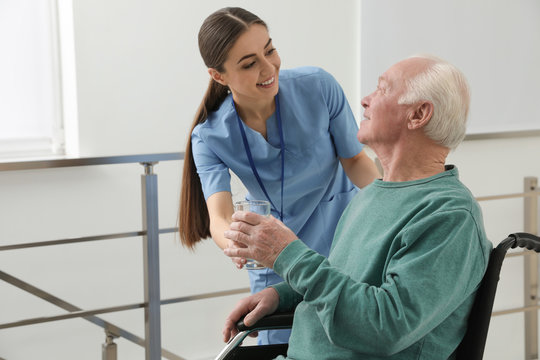 Nurse giving water to senior man in wheelchair at hospital. Medical assisting
