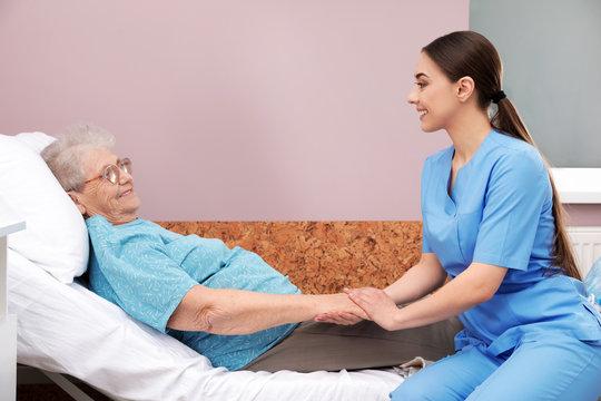 Nurse assisting senior woman lying on bed in hospital ward
