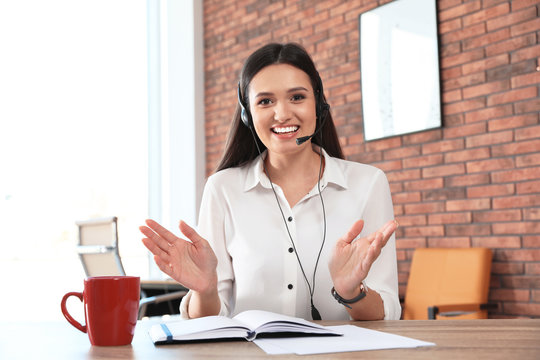 Young woman with headset looking at camera and using video chat in home office