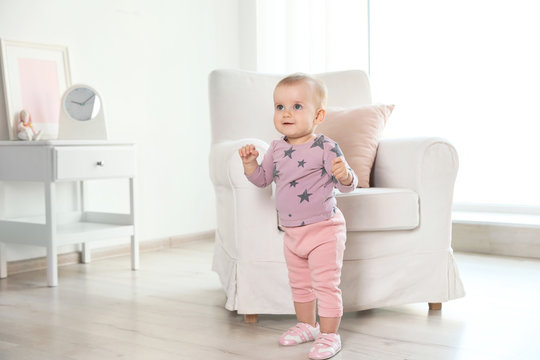 Cute baby girl standing near armchair in room