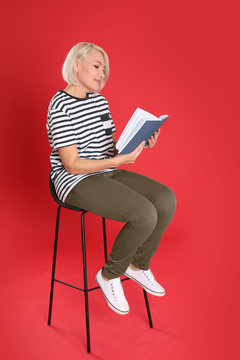Senior woman reading book on color background