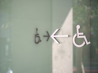Wheelchair disabled logos with arrow showing path to entrance outside of modern glass building