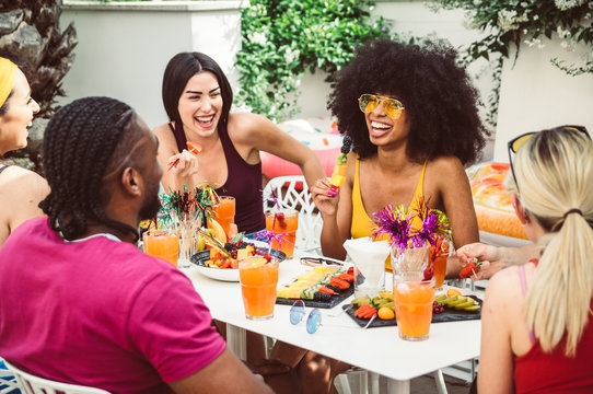 Group of happy multiracial friends talking and laughing having a conversation at lunch
