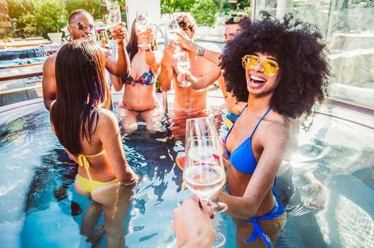 Happy multiracial friends having fun on a pool party on vacation