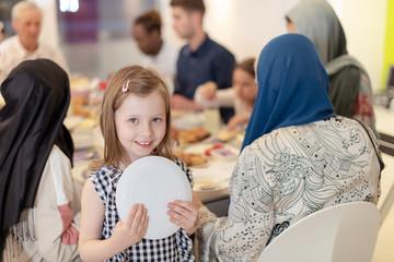 cute little girl enjoying iftar dinner with family