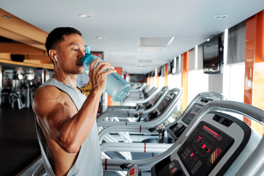 Muscular Asian sportsman drinking water after running on treadmill in gym