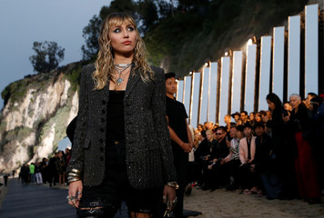 Miley Cyrus looks on at the Saint Laurent Men's Spring/Summer 2020 fashion show at Paradise Cove beach in Malibu