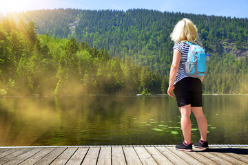 Woman by the moraine lake Grosser Arbersee in the National park Bavarian forest. Germany.