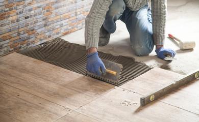 Obraz Laying floor ceramic tile. Renovating the floor - fototapety do salonu