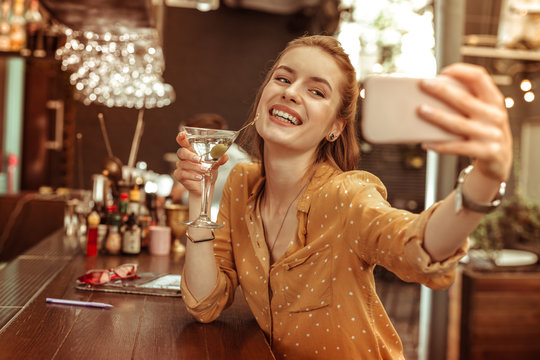 Glowing lady taking selfies while being at the bar with a drink.