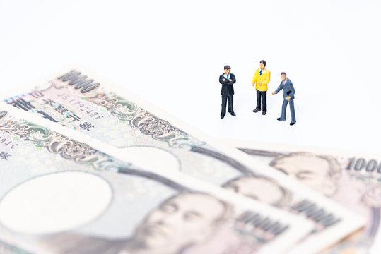 お金とビジネスマンのフィギュア