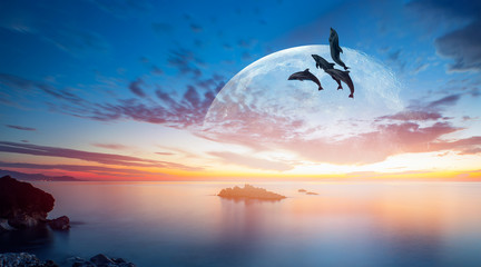 "Silhoutte of beautiful dolphin jumping up from the sea at sunset with super moon ""Elements of this image furnished by NASA """